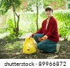 woman fertilizes the soil in garden - stock photo