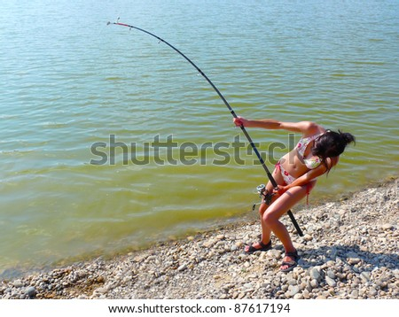 Woman fighting with a big catfish