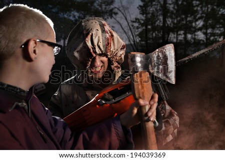 Woman fights with the maniac, axe against chainsaw