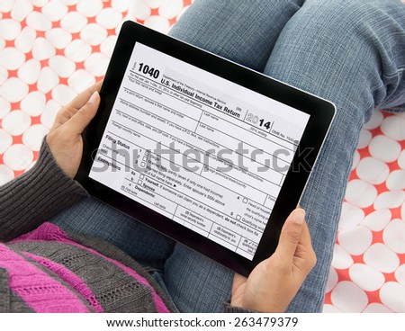 Woman  filing federal income tax over internet using form 1040 on mobile tablet computer and wireless technology - stock photo