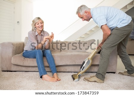 Woman filing nails while man using vacuum on area rug in the living room at home