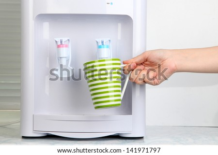 Woman filling cup at water cooler