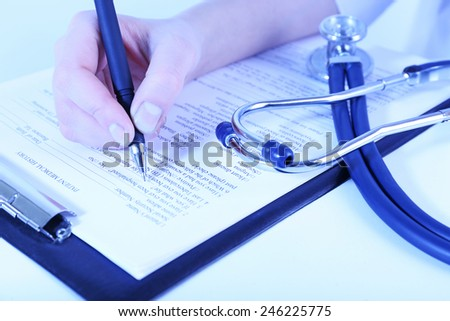 Woman filling medical history on light background - stock photo