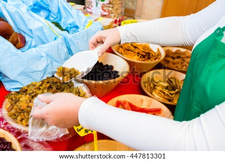 Woman filling meze starters in container - stock photo