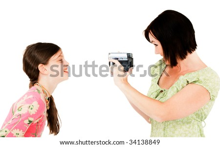 Woman filming a girl with a home video camera isolated over white - stock photo