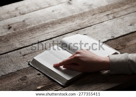 woman finger presses on bible book over wooden background - stock photo