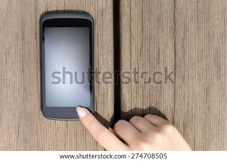 Woman finger pressing a blank smart phone touch screen with wooden background - stock photo
