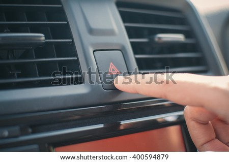 Woman finger pressing emergency button on car dashboard - stock photo