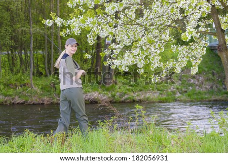 woman fishing by the river in spring