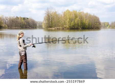 woman fishing in pond - stock photo