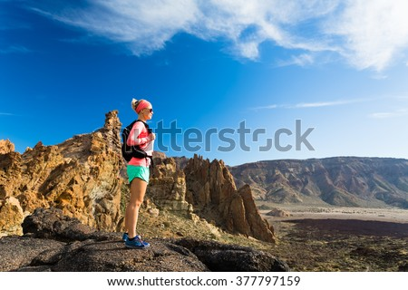 Woman fit hiker or trail runner looking at beautiful inspirational landscape in mountains. Beauty female runner, happiness and enjoying inspiring view on rocky trail footpath, Tenerife Canary Islands - stock photo