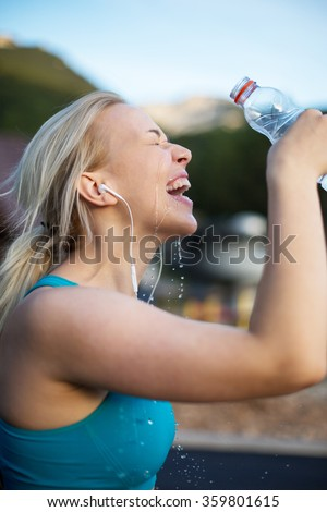 Woman fitness runner drinking and splashing water in her face. Funny image of beautiful female fitness model on black background.