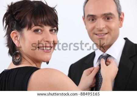 Woman fixing a man's tie - stock photo