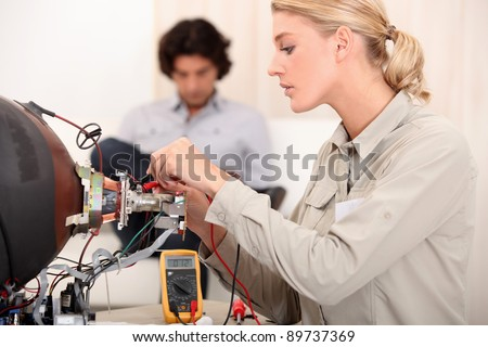 Woman fixing a television