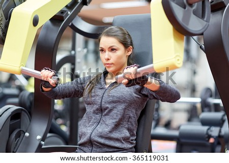 woman flexing muscles on chest press gym machine  - stock photo