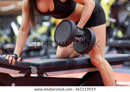 woman flexing muscles with dumbbell in gym - stock photo