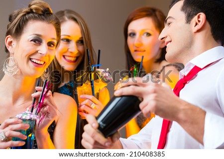 Woman flirting with barkeeper in cocktail bar - stock photo