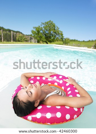 Woman floating in a pink polka dot inner tube with eyes closed. Vertical. - stock photo