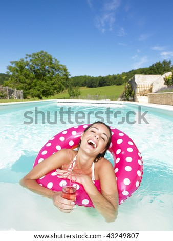 Woman floating in an inner tube in a swimming pool and laughing with drink in hand. Vertical. - stock photo