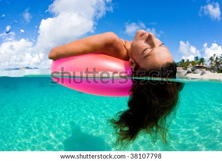 woman floating on inflatable inner tube in tropical beach waters relaxing and dreaming