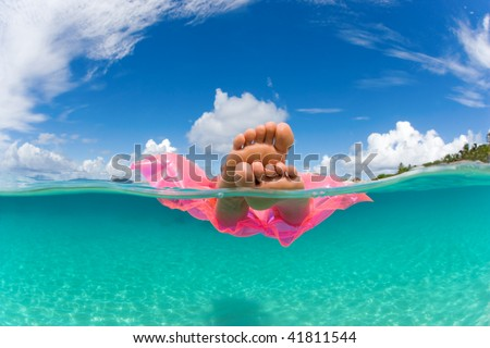 woman floating on inflatable raft relaxing and sunbathing in tropical water with feet showing under over