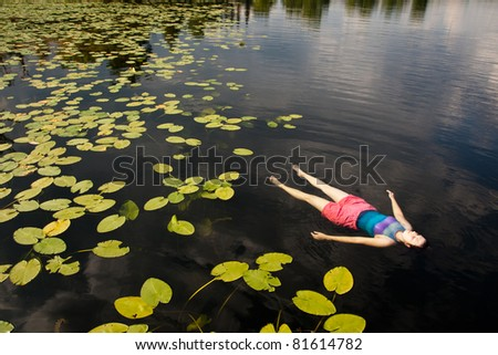 Woman Floating on Lake with Lily Pads - stock photo