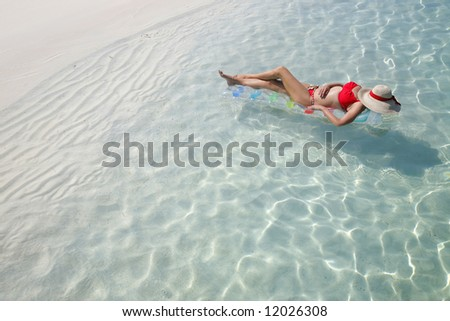 Woman floating on lilo in tropical lagoon