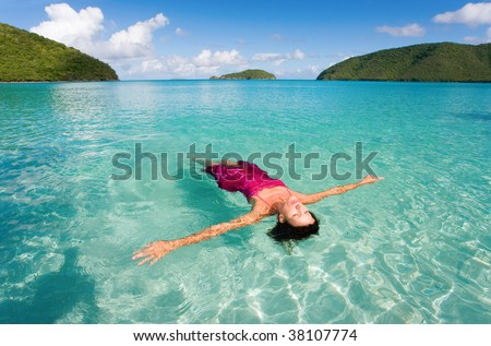 woman floating with sarong in turquoise waters at colorful tropical beach - stock photo