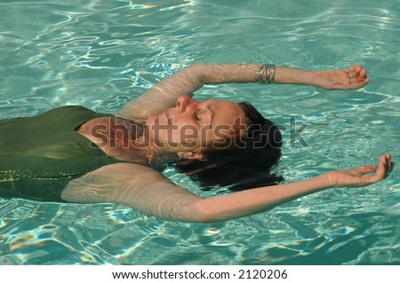 Woman floats in pool on her long awaited vacation - stock photo