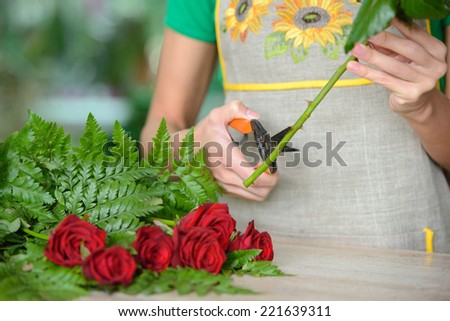 Woman florist preparing bouquet flowers shop retail arranging - stock photo