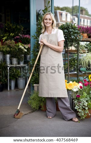 Woman florist standing at the entrance to her shop, leaning on a broom - stock photo