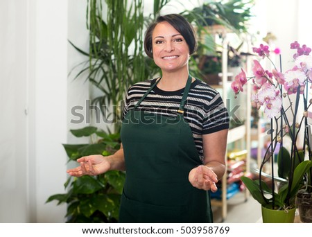 Woman florist wearing an apron and working in the floral shop and smiling