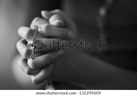 Woman folding hands and praying to God. - stock photo