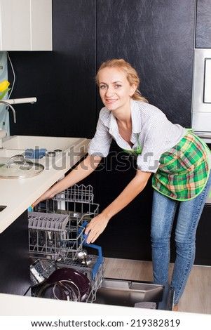 Woman folding the dishes in the dishwasher. Female at kitchen