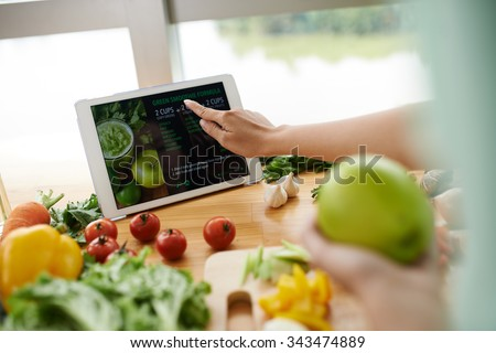 Woman following recipe on website to make healthy smoothie - stock photo