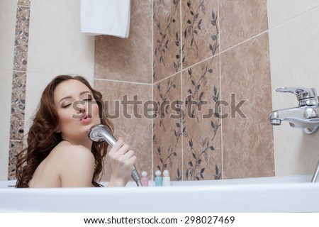 Woman fooling around while singing in bathroom - stock photo