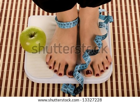 Woman foot on measuring scale with tape and apple. - stock photo