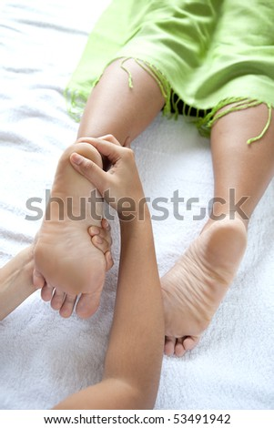 Woman foot reflexologist giving woman client a foot reflexology - stock photo