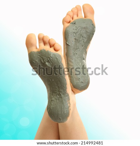 Woman foots with cosmetic clay on bright background - stock photo