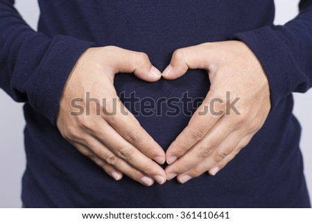Woman Forming Heart Shape on Belly - stock photo
