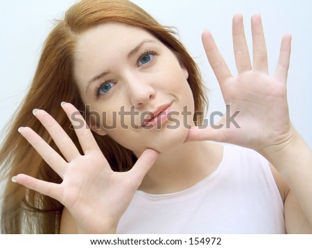 Woman framing her face with her hands. - stock photo