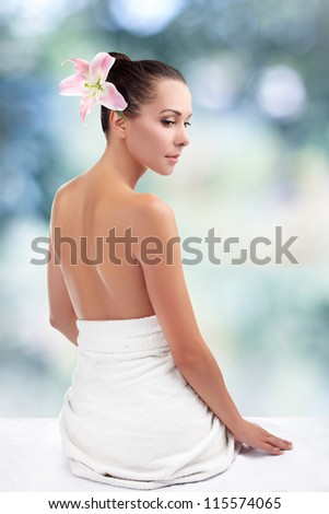 Woman from behind, naked body, against abstract blue background - stock photo