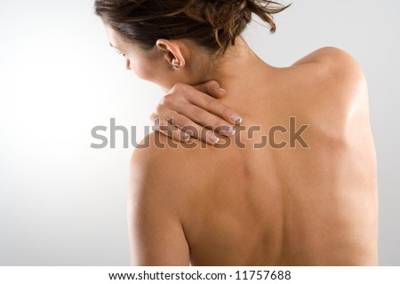 Woman from behind, naked body, holding her neck on the left side. Face to the left. Body tensed. - stock photo