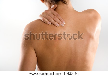 Woman from behind, naked body, holding her neck on the left side. Nearly no head. - stock photo