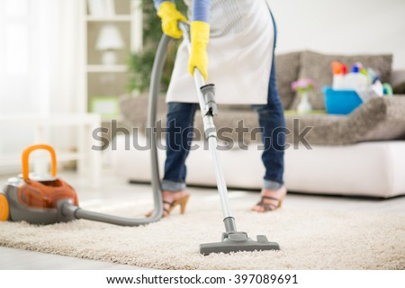 Woman from cleaning service cleans carpet with vacuum cleaner - stock photo