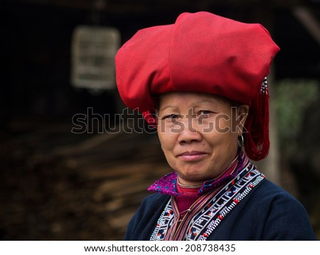 Woman from Red Dao minority group wearing traditional attire and headdress in Sapa, Lao Cai Province, Vietnam.