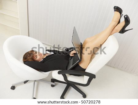 Woman funny is located in two office chairs with laptop - stock photo