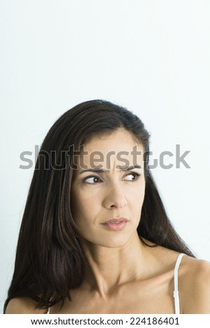 Woman furrowing brow, looking away, portrait - stock photo