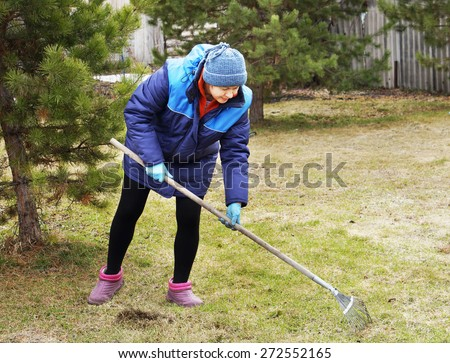 Woman gardener cleans a garden with the rake in spring - stock photo