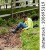 Woman gardener sits on grass when weeding flowerbed - stock photo